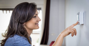women changing setting on home thermostat