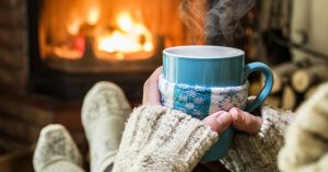 woman in sweater drinking hot chocolate near fire