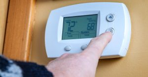 Person turning up the heat on thermostat