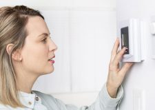 Woman adjusting heat temperature on thermostat