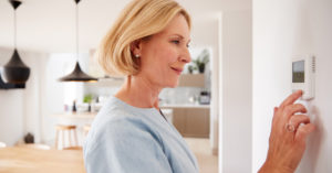 Woman adjusting thermostat to heat home