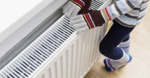 woman with gloves on because of heating problem